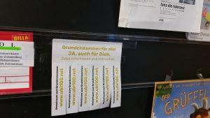 Werbung zum BGE im Supermarkt aufhängen